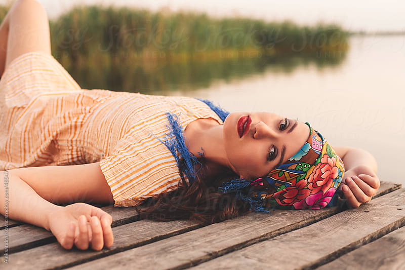 Woman laying on the dock by the lake by Aleksandra Kovac for Stocksy United