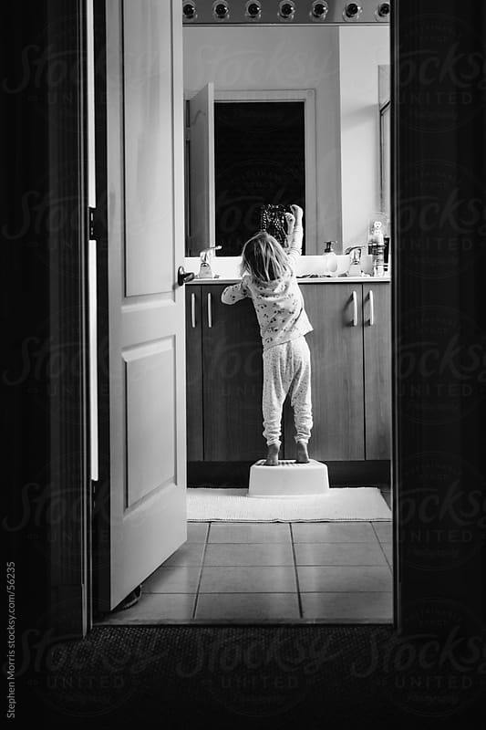 Girl Playing with Mother's Jewelry in Bathroom by Stephen Morris for Stocksy United