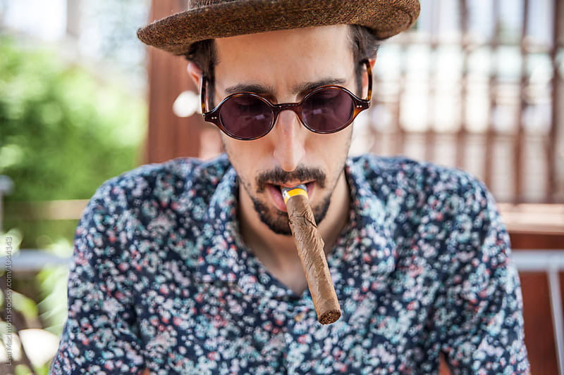 young man with cigar in his mouth by Lisa MacIntosh for Stocksy United