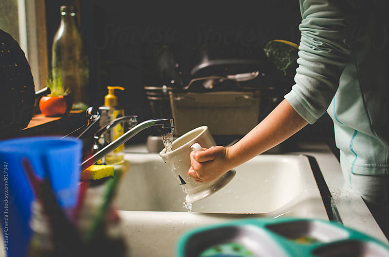Child washing dishes by Lindsay Crandall for Stocksy United