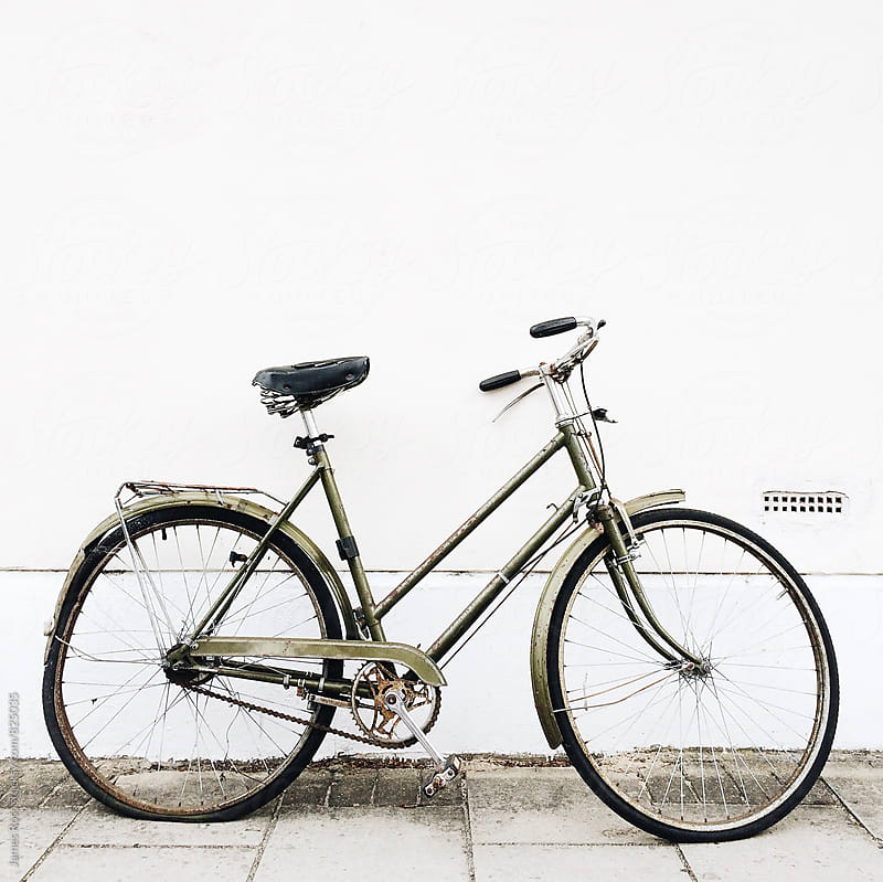 An old bike left against a white wall by James Ross for Stocksy United