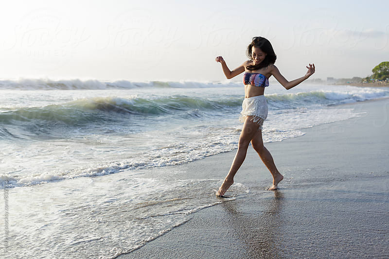 Young asian woman at beach by Felix Hug for Stocksy United