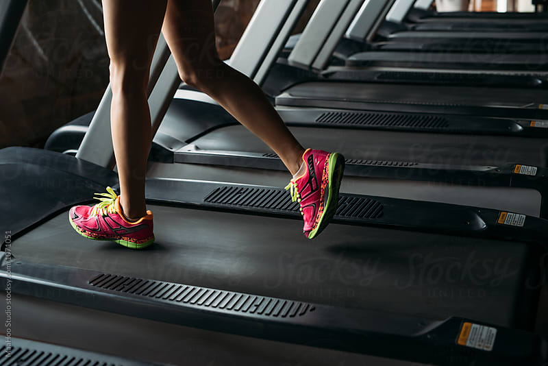 Young woman running on treadmill in gym by Maa Hoo for Stocksy United