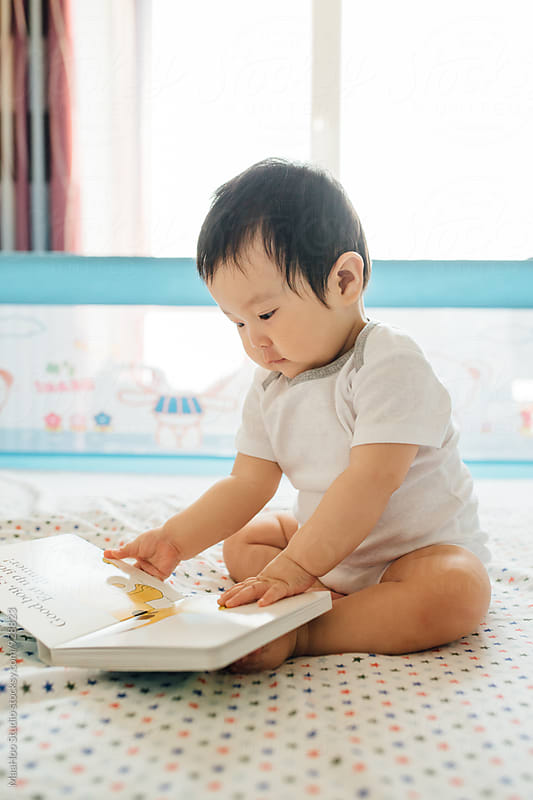 A Chinese baby boy sitting on be and reading books by MaaHoo Studio for Stocksy United
