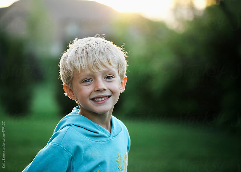 portrait of a happy boy at sunset by Kelly Knox for Stocksy United