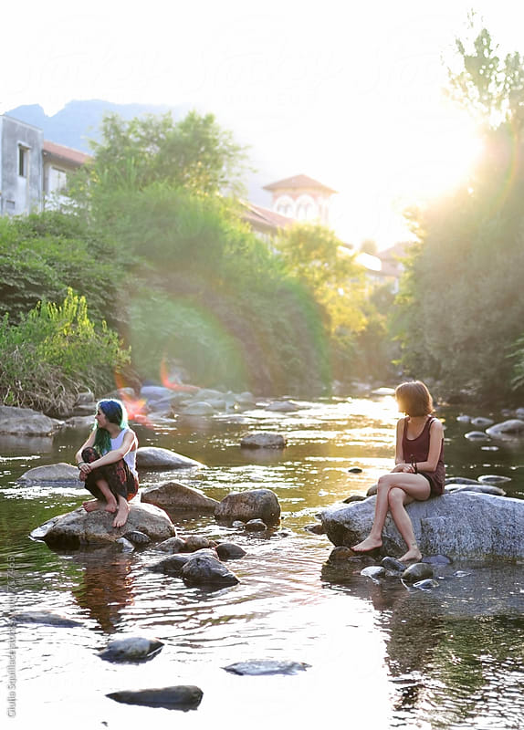 Young women sitting on the stones in a river by Giulia Squillace for Stocksy United