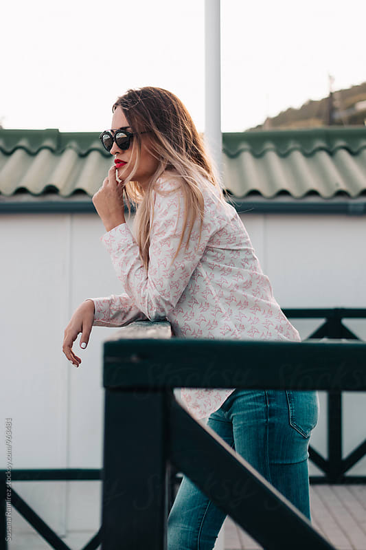 Cool woman with sunglasses leaning on railing by Susana Ramírez for Stocksy United