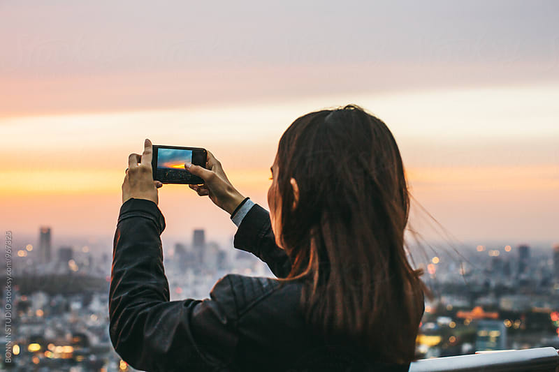 Back view of a woman taking photo on her phone of Tokyo skyline. by BONNINSTUDIO for Stocksy United