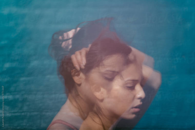 Double exposure of woman pulling her hair back by Lauren Naefe for Stocksy United