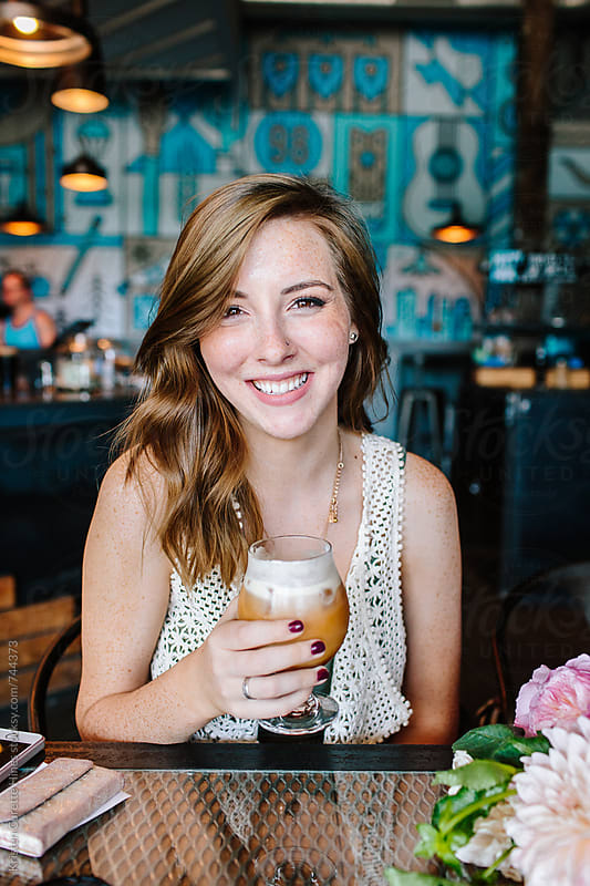 A pretty young girl enjoying an iced latte at a coffee shop / cafe by Kristen Curette Hines for Stocksy United