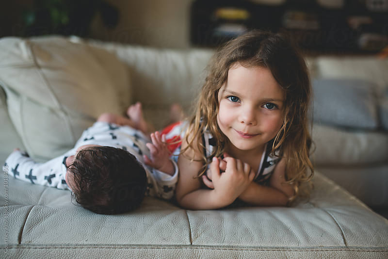 young toddler girl and her newborn baby by Courtney Rust for Stocksy United