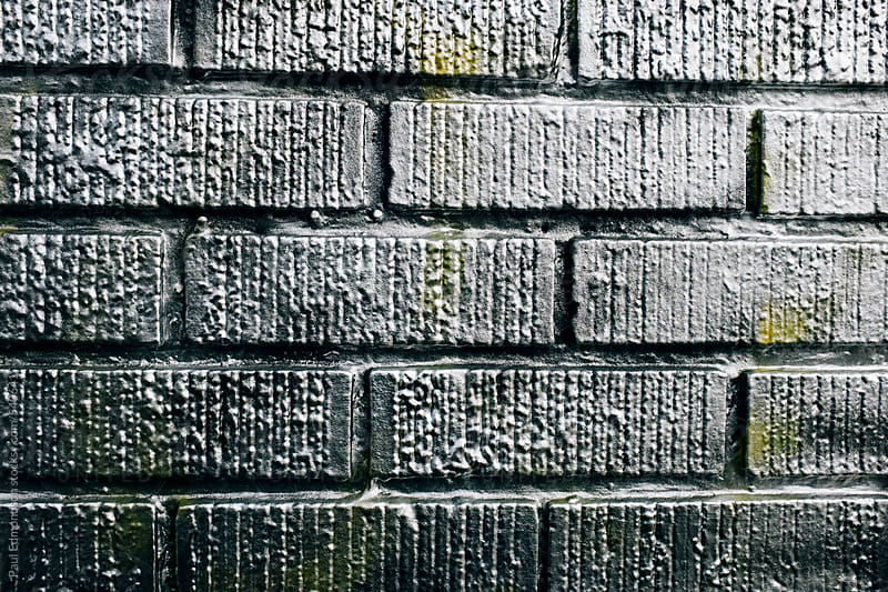 Metallic silver spray paint covering graffiti tags on brick wall by Paul Edmondson for Stocksy United