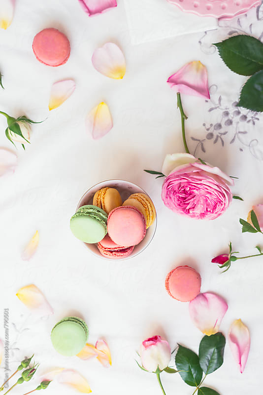 small bowl of macarons sitting amongst a scattering of rose petals by Gillian Vann for Stocksy United