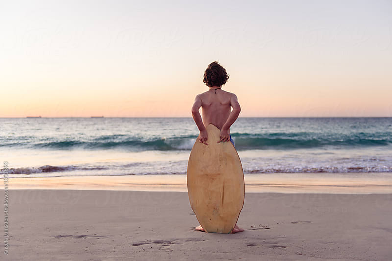 Boy standing with skim board at the beach by Angela Lumsden for Stocksy United