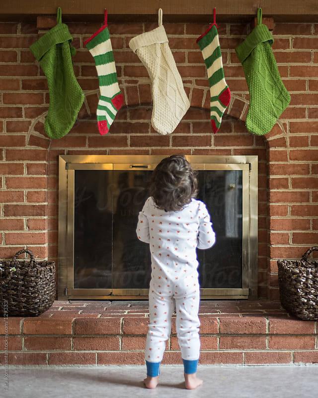 boy in pajamas looks up at christmas stockings by Tara Romasanta for Stocksy United