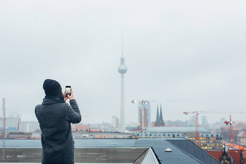 Woman Taking Cellphone Photo of Berlin's TV Tower on Rainy Winter Day by Julien L. Balmer for Stocksy United