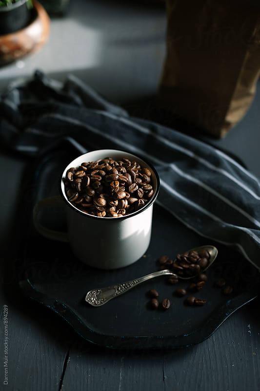 Coffee beans in an enamel mug. by Darren Muir for Stocksy United