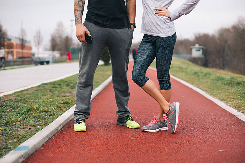 Handsome couple in sportswear standing on a jogging track by Marija Mandic for Stocksy United