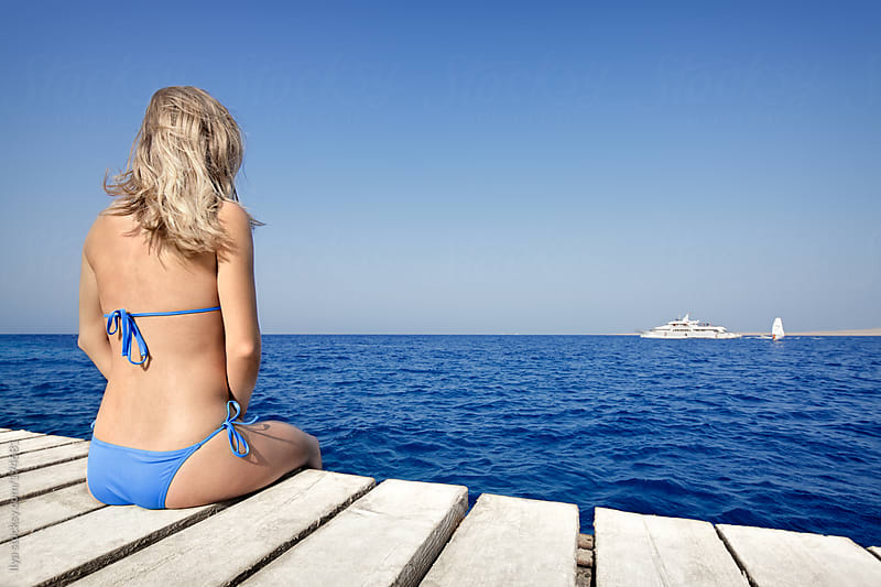 Young woman in bikini sitting on pier looking at sea. by Ilya for Stocksy United