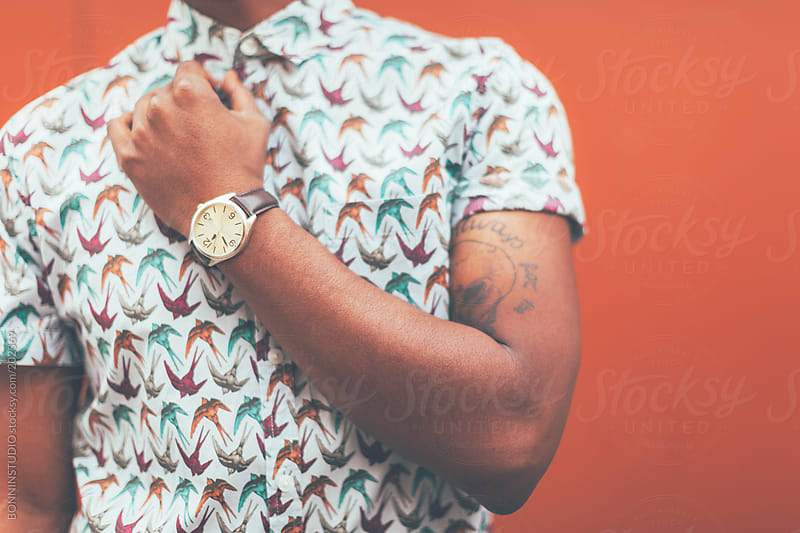 Cropped view of modern young black man in front a orange wall. by BONNINSTUDIO for Stocksy United