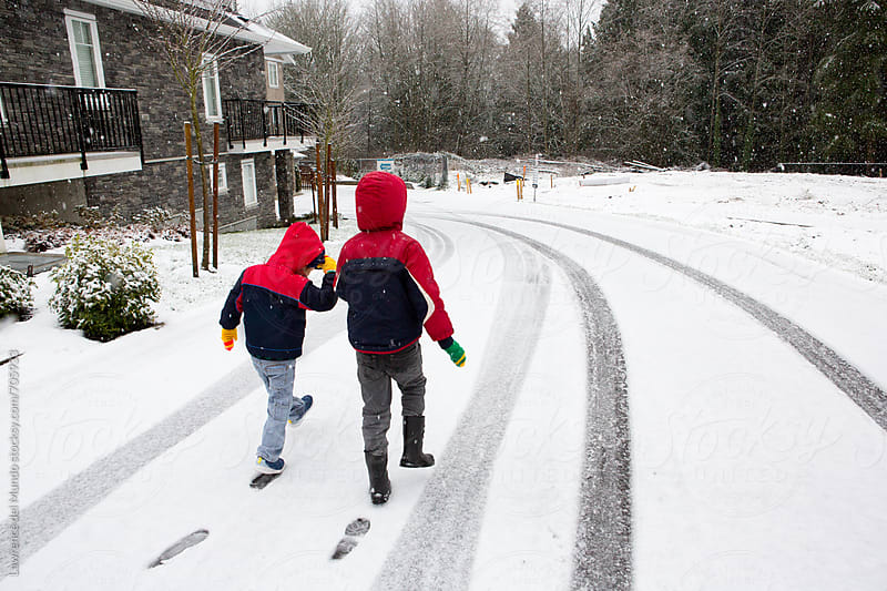 Two boys walking on snow and leaving their footprints.  by Lawrence del Mundo for Stocksy United