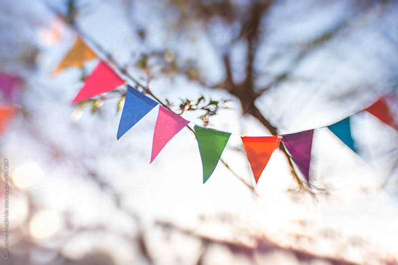 Bunting fluttering in the breeze... by Catherine MacBride for Stocksy United