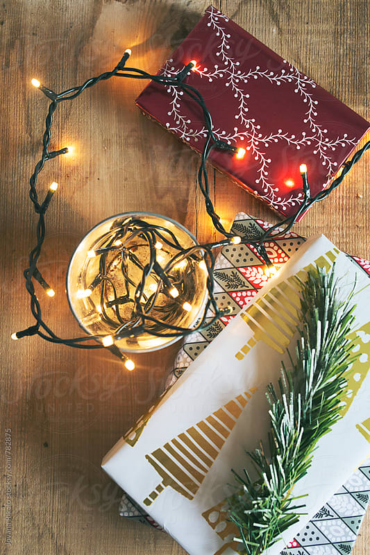 Christmas lights and gifts on a wooden background by Jovana Rikalo for Stocksy United