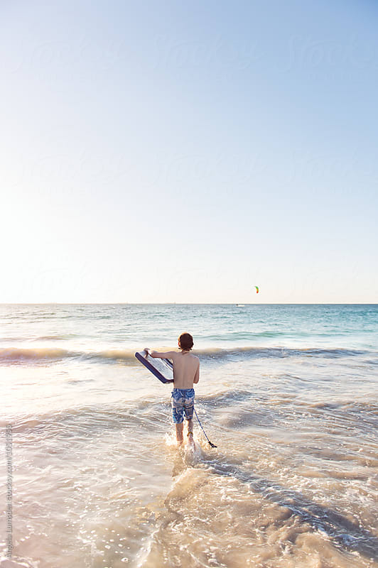 Boy standing holding a boogie board and assessing the waves at the beach by Angela Lumsden for Stocksy United
