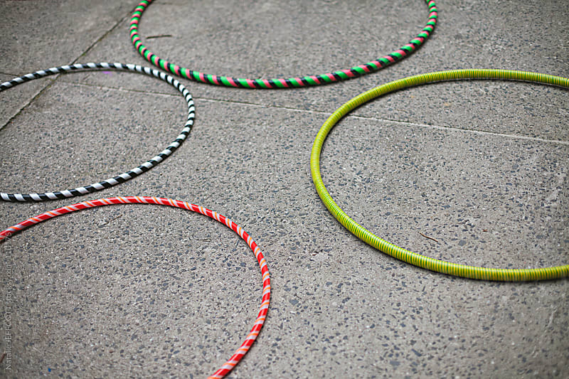 colourful hula hoops discarded on the ground by Natalie JEFFCOTT for Stocksy United