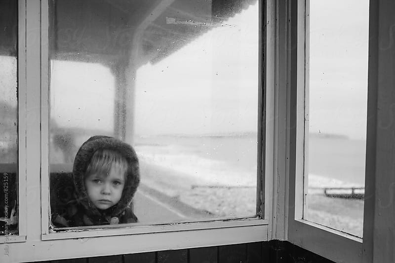 Small child looks through the windows of a seaside shelter in winter. by Julia Forsman for Stocksy United