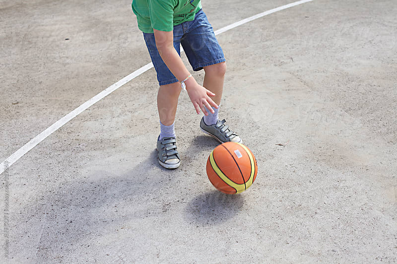 close up of young boy playing basketball by Natalie JEFFCOTT for Stocksy United