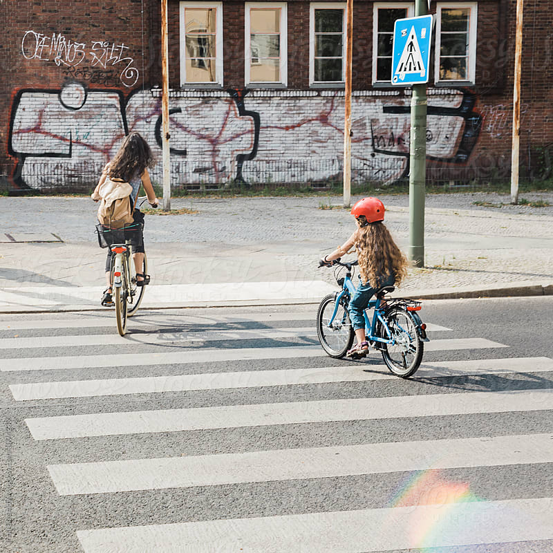Mother and daughter crossing the road on the bicycles  by Irina Efremova for Stocksy United