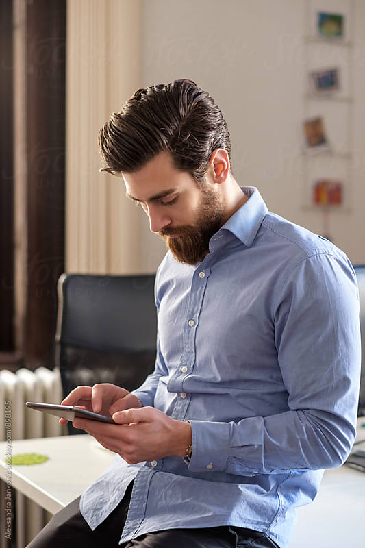 Handsome Man Using Tablet Computer at the Office by Aleksandra Jankovic for Stocksy United