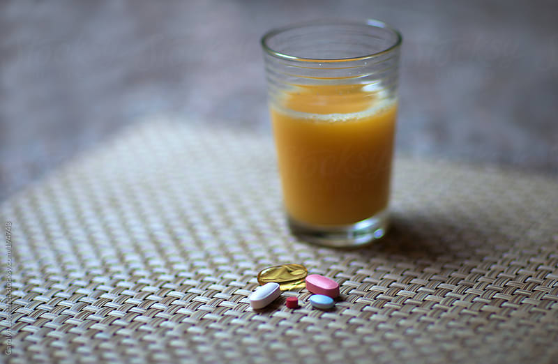 Orange juice and an assortment of vitamins and pills by Carolyn Lagattuta for Stocksy United