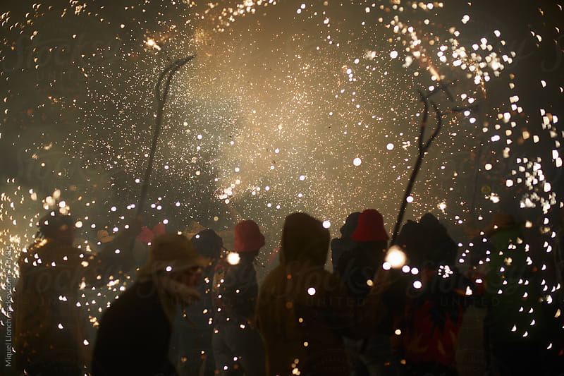 People crowd in a spectacular fire parade by Miquel Llonch for Stocksy United