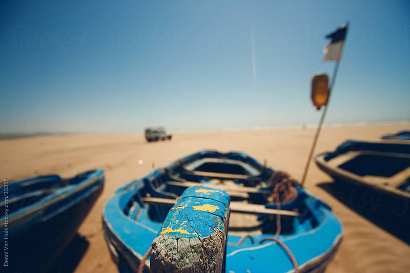 A wooden boat docked on a dry beach waiting for high tide by Denni Van Huis for Stocksy United