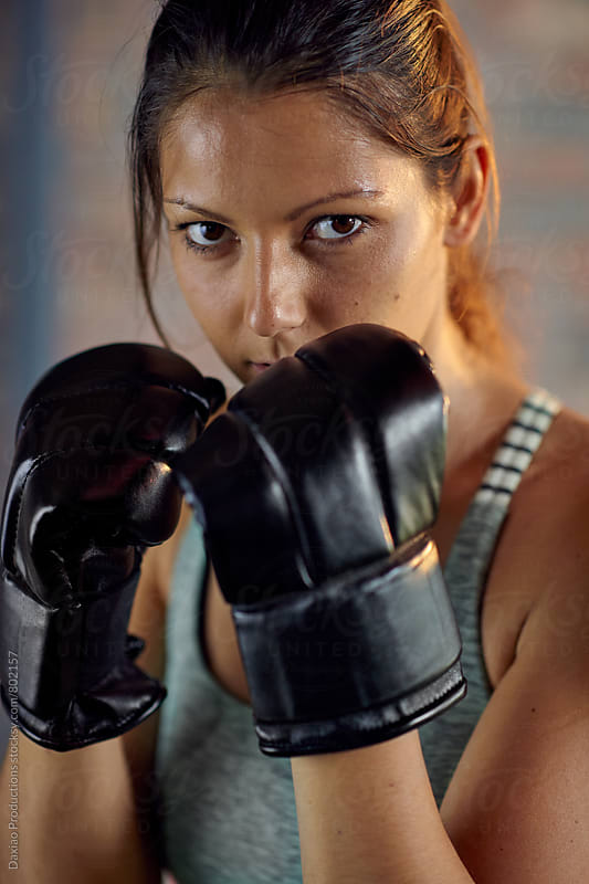 Fitness muscular lean woman boxer in black boxing punching gloves by Daxiao Productions for Stocksy United