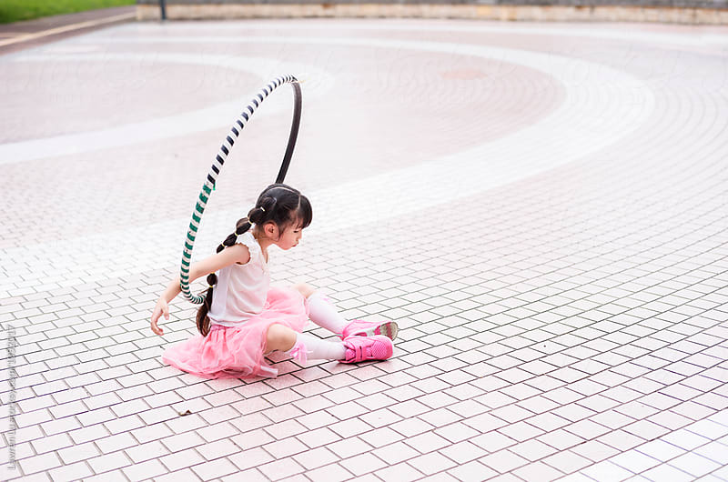 Side view of black-haired girl with hulahoop on pavement by Lawren Lu for Stocksy United