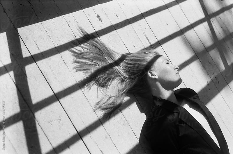 A film portrait of blond woman lying on the wood floor by Anna Malgina for Stocksy United