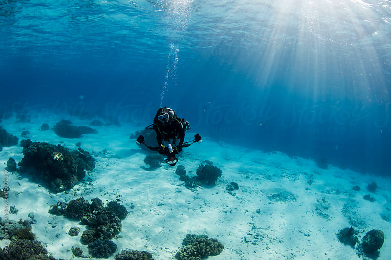 underwater photographer under surface with sunlight by Song Heming for Stocksy United