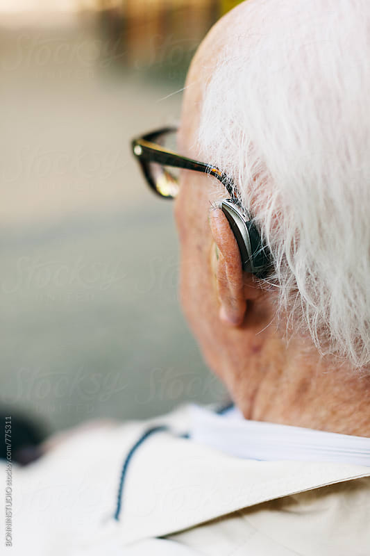 Back view of an elderly man with a hearing aid. by BONNINSTUDIO for Stocksy United