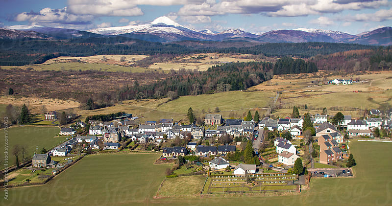 An aerial landscape view of a small Scottish village with mountains and clouds in the background by Andy Campbell for Stocksy United