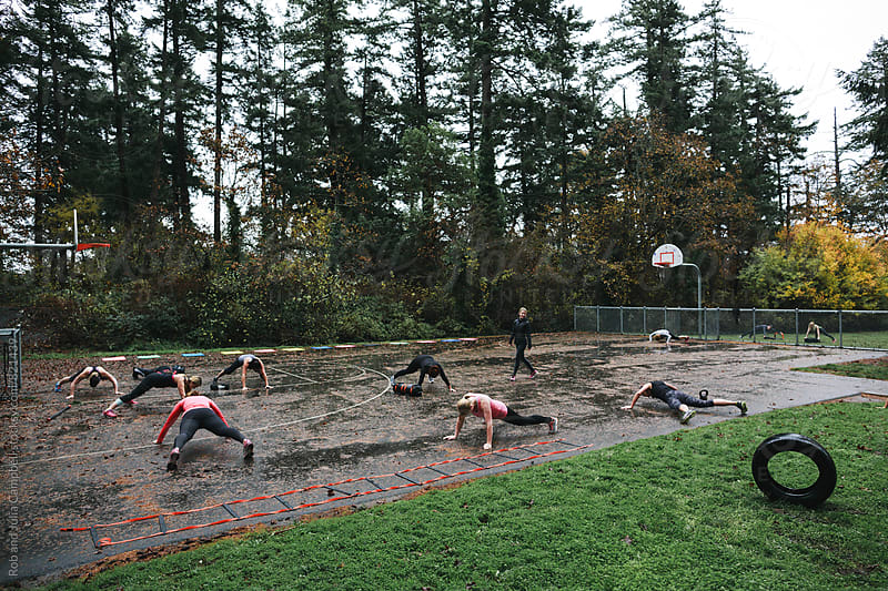Group of fit people working out - planks - together at outdoor boot camp by Rob and Julia Campbell for Stocksy United