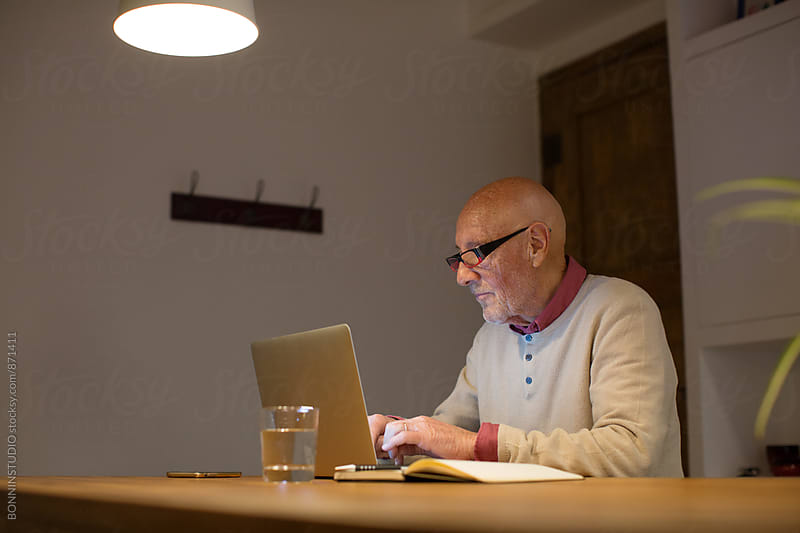 Elderly man typing on his laptop at home office in the late afternoon. by BONNINSTUDIO for Stocksy United