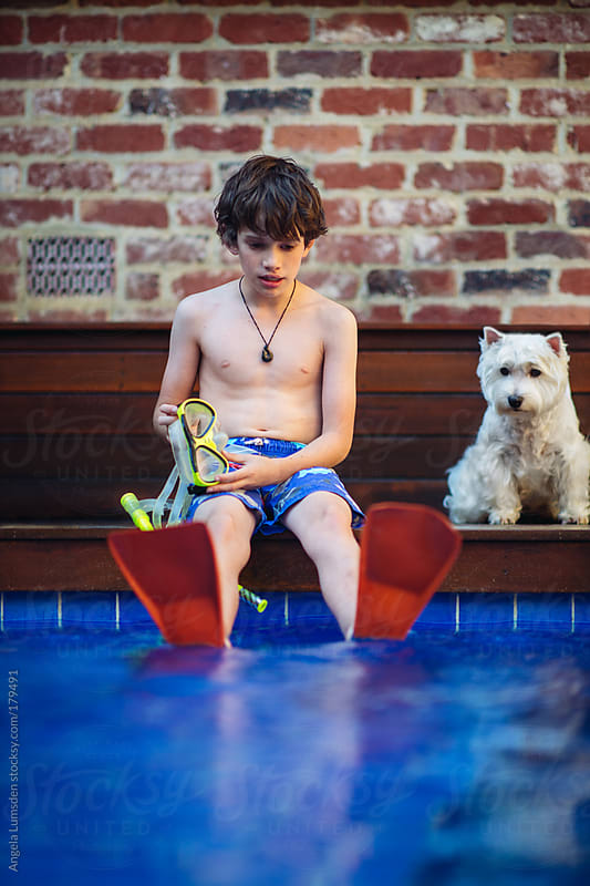 Boy with snorkel set sitting on the side of a pool by Angela Lumsden for Stocksy United