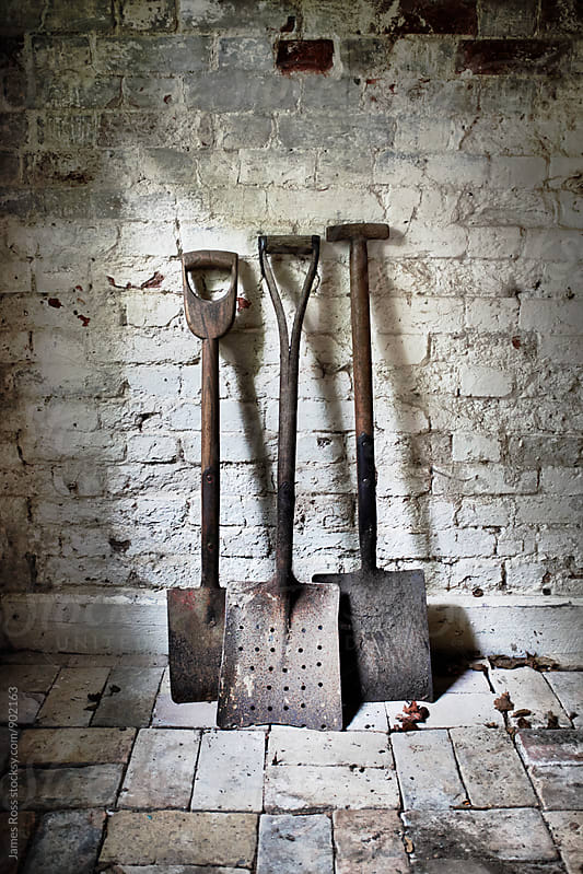 Three shovels by a brick wall by James Ross for Stocksy United