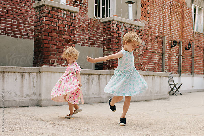 A brother and sister wearing pretty dresses spin on an urban rooftop. by Julia Forsman for Stocksy United
