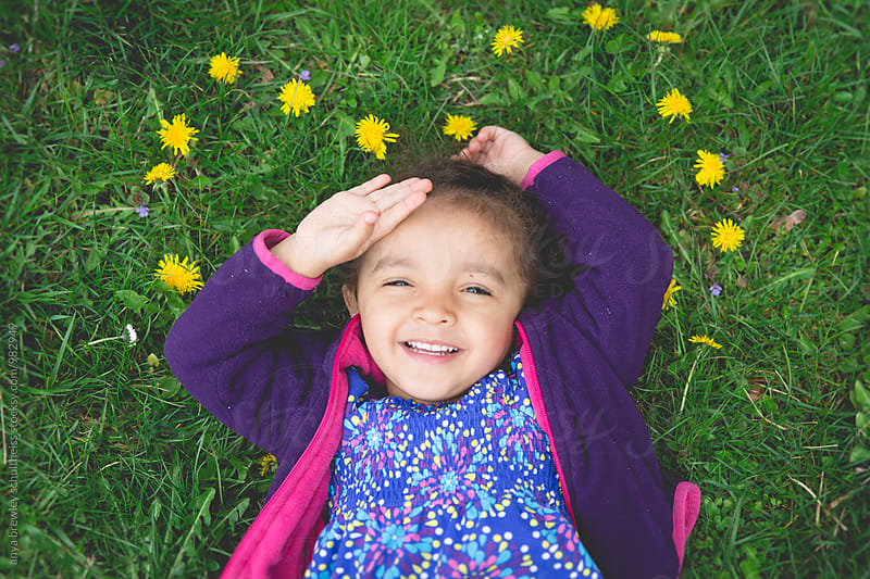 Portrait of a cute young child lying down on a green lawn surrounded by flowers by anya brewley schultheiss for Stocksy United
