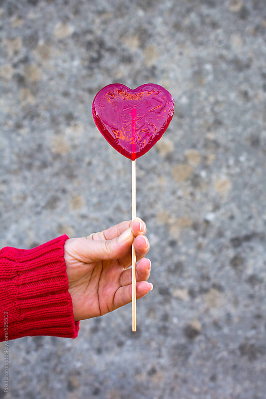 Hand holding heart-shaped lollipop by Pixel Stories for Stocksy United