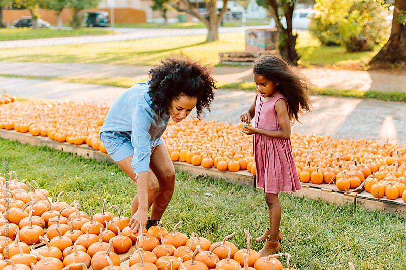 Mother and daughter in pumpkin patch by Kristen Curette Hines for Stocksy United